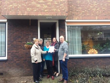 Uitreiking van het rapport van het onderzoek naar het wonen in de verbeterde woning aan de familie Meurs.